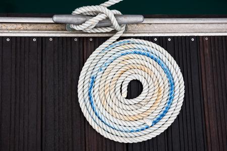 bateau: Une corde d'amarrage avec une extr�mit� nou�e autour d'un taquet attach� sur une jet�e en bois Banque d'images