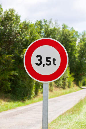 tons: Traffic sign of 3,5 tons weigh restriction on a rural road background Stock Photo