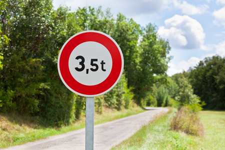 restriction: Traffic sign of 3,5 tons weigh restriction on a rural road background Stock Photo