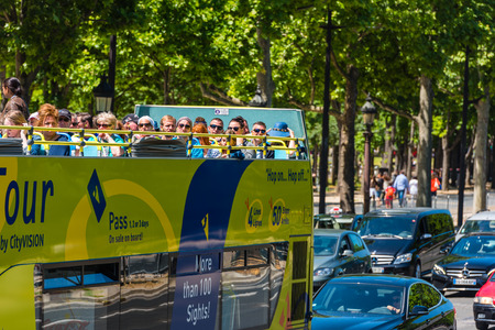 sightseeing tour: FRANCE, PARIS - JUNE 06: Tourists enjoy sightseeing tour on a hop-on-hop-off city bus in Paris on June 06, 2015.