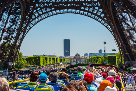 sightseeing tour: FRANCE, PARIS - JUNE 06: Tourists enjoy sightseeing tour on a hop-on-hop-off city bus in Paris on June 06, 2015. Bus is under The Eiffel tower. Editorial