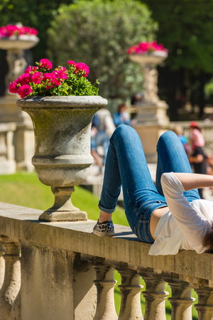 girl lying down: A young woman in jeans is lying and relaxing in a park on a sunny summer day