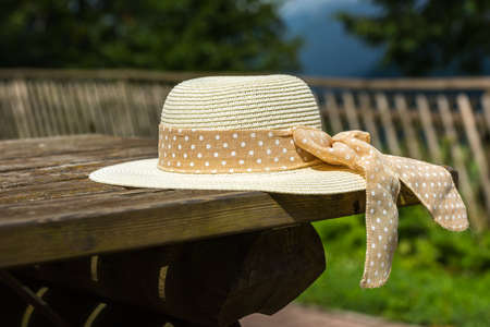 focus shot: Female summer hat laying on the wooden rustic table. Selective focus shot Stock Photo