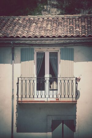 balcony window: House facade with window and balcony in Southern France. Vertical filtered shot