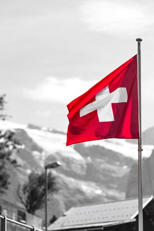 partly: Swiss flag against Alps mountains. Partly colored shot