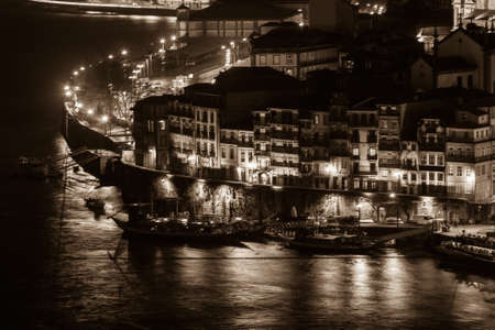 ribeira: Overview of Old Town of Porto, Portugal at night. Ribeira and Douro river filtered in sepia