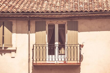 balcony window: House facade with window and balcony in Southern France. Horizontal filtered shot