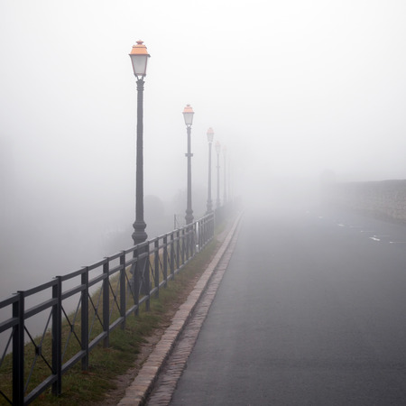 vanish: Foggy road with old lamps. France, Saint-Emilion. Square image Stock Photo