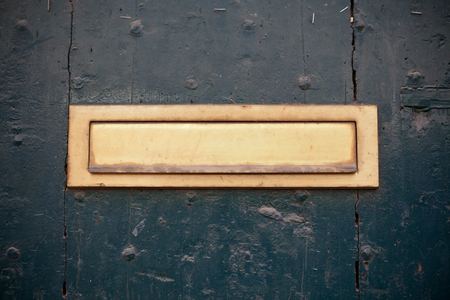 Dark green door with letter slot mailbox. Horizontal shot