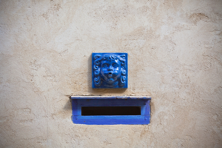 Plaster wall with blue decorative letter slot mailbox. Horizontal shot