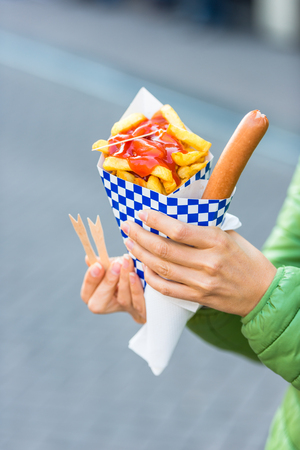hot sauce: Female hands holding paper cone with a hot sausage and french fries with ketchup