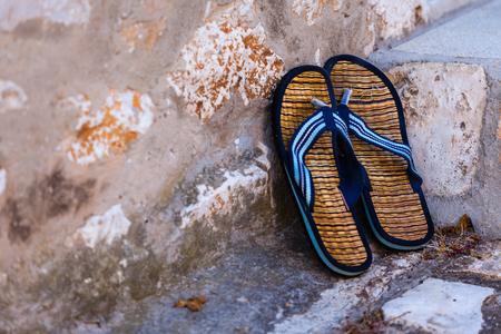 flipflops: Beach flip-flops on the old wall background. Horizontal shot