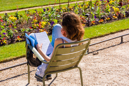 french woman: FRANCE, PARIS - JUNE 06: Young french woman sitting on a chair in the park and reading a book on June 06, 2015