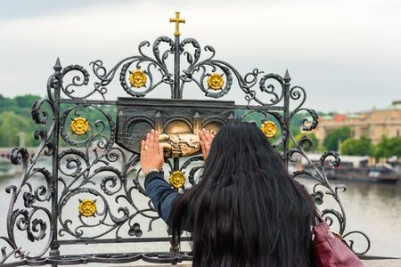 back rub: THE CZECH REPUBLIC, PRAGUE - MAY 19: Woman touching the sculpture of Saint Jan Nepomuk on the Charles bridge in Prague, Czech on May 19, 2015