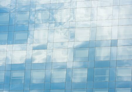 window reflection: blue sky and clouds reflected in windows of modern office building