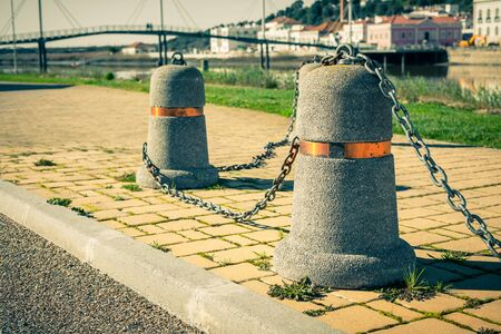 linked: Stub posts linked in a chain on a quay in a small Portugal town