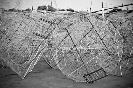 trawl: Metal fishing nets in a port. Horizontal bw toned shot Stock Photo