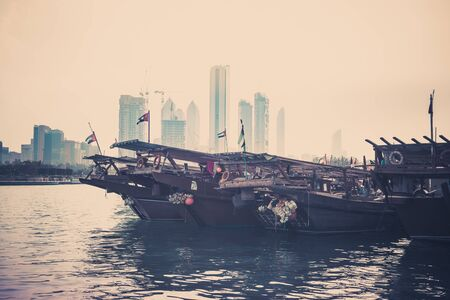 abu dhabi: Abu Dhabi buildings skyline with old fishing boats on the front. Filtered shot Stock Photo