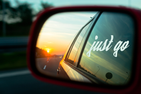 Motivation quote Just go with Sunset reflection in the rear view mirror of a car on a highway Stock Photo