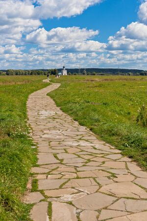 bogolyubovo: Way through a field to The Church of the intercession on the Nerl river in Russia the village Bogolyubovo Stock Photo