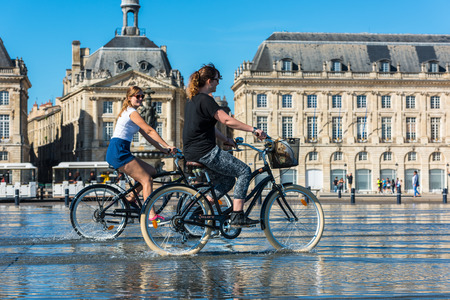 gironde: FRANCE, BORDEAUX - SEPTEMBER 20: People riding bicycles in the mirror fountain in front of Place de la Bourse in Bordeaux, France on September 20, 2015