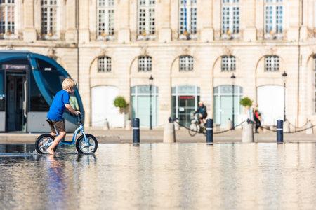 gironde: FRANCE, BORDEAUX - SEPTEMBER 20: Children having fun in a mirror fountain in front of Place de la Bourse in Bordeaux, France on September 20, 2015