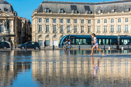 gironde: FRANCE, BORDEAUX - SEPTEMBER 20: People having fun in a mirror fountain in front of Place de la Bourse in Bordeaux, France on September 20, 2015 Editorial