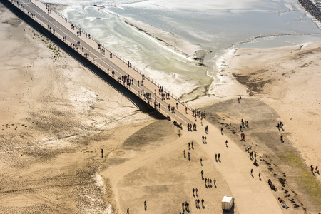 michel: View from walls of Mont Saint Michel on the bay during the low tide. Groups of tourists walking. France Stock Photo