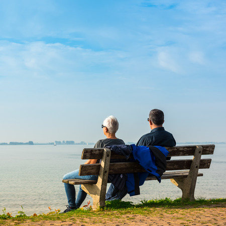 marken: NETHERLANDS, MARKEN - OCTOBER 3: happy romantic middle aged couple enjoying sea view sitting on the bench on October 3, 2015 Editorial