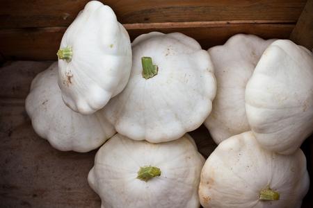 cymbling: White custard marrows in a wooden box on a farm market Stock Photo