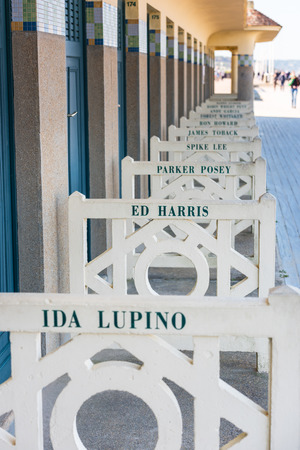 ida: FRANCE, DEAUVILLE - SEPTEMBER 27: original beach closets with famous names on promenade Des Planches in Deauville, France on September 27, 2015