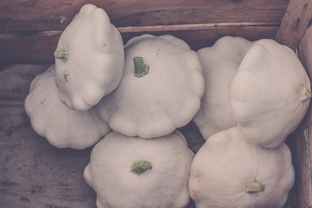 cymbling: White custard marrows in a wooden box on a farm market. Filtered shot