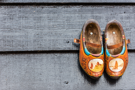 wooden shoes: Traditional dutch wooden shoes hanging at a wall. Background Stock Photo