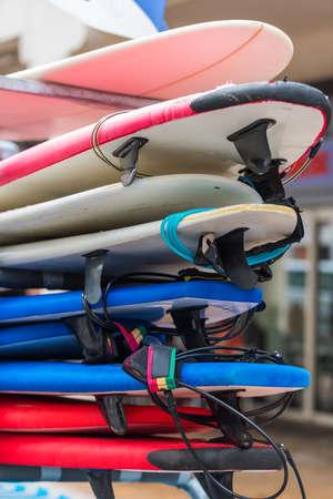 surf shop: set of different color surf boards in a stack. France