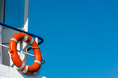 lifeline: Bright orange lifebuoy on a white yacht side. Blue sky background Stock Photo