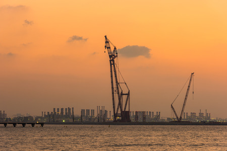 seaport: Sunset at the Dubai seaport, UAE. Silhouette of cranes on a bright sky background Stock Photo