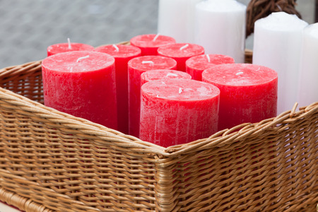 beeswax candle: Wicker basket with red and white round candles in a shop. Horizontal shot Stock Photo