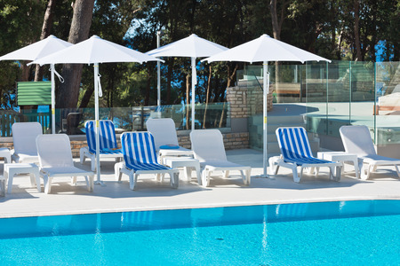 poolside: Hotel Poolside Chairs with Sea view. Summer shot