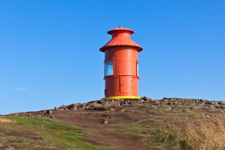 over the edge: Red Lighthouse on a hill above Stykkisholmur, the western part of Iceland Stock Photo