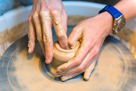 womens hands of a potter creating an earthen jar Stock Photo