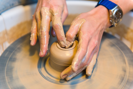 womens hands of a potter creating an earthen jar Foto de archivo