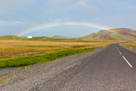 Rainbow and Endless Highway through Icelandic landscape. Filtered shot