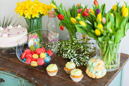 Bright macaroons and cupcakes on a wooden table. Indoors natural light shot with small depth of field