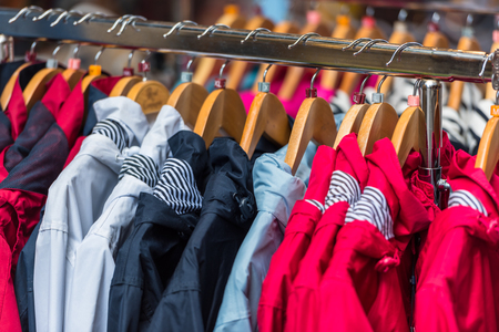 sport clothes: Bright autumn raincoats hanging at a fashion store
