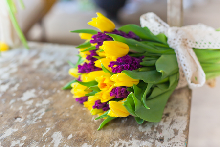 Yellow tulips and purple hyacinths flowers bouquet on a wooden table. Indoors natural light shot with small depth of field