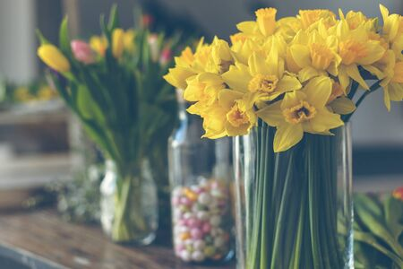 Yellow narcissuses bouquet in a glass vase. Indoors natural light shot with small depth of field