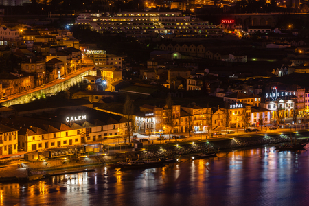 PORTUGAL, PORTO - JANUARY 20: Overview of Vila Nova de Gaia, district of Porto, Portugal at night on January 20, 2013. The world famous Port wine is stored here. Editorial