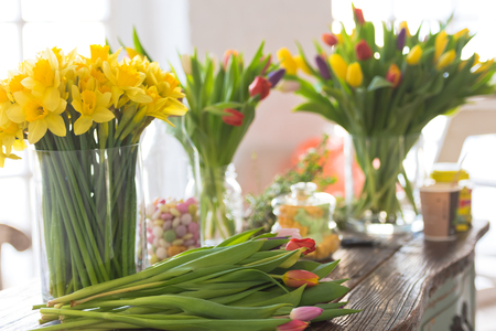 Spring flowers on a wooden table. Indoors natural light shot with small depth of field Stock Photo