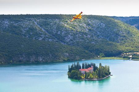 Firefighting plane training near the island and monastery Vysovas, Krka park in Croatia