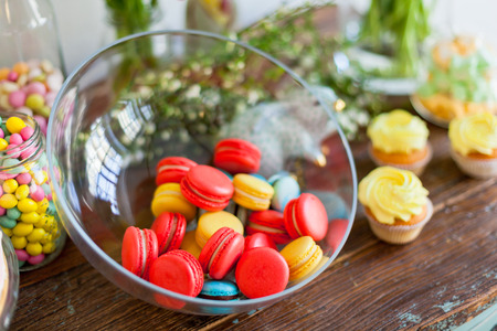 easter cookie: Bright macaroons and cupcakes on a wooden table. Indoors natural light shot with small depth of field
